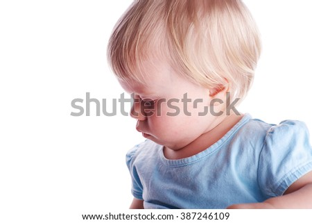 Side view at portrait of adorable little baby girl in the blu t-shirt in the studio, isolated on white background - stock photo
