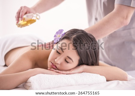 Side view. Beautiful asian woman having massage with spa oil in beauty salon. - stock photo