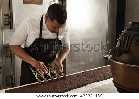 Side view black man chief use professional vintage separator to split chocolate cake on equal portions before packaging, artisan cooking process in confectionery - stock photo