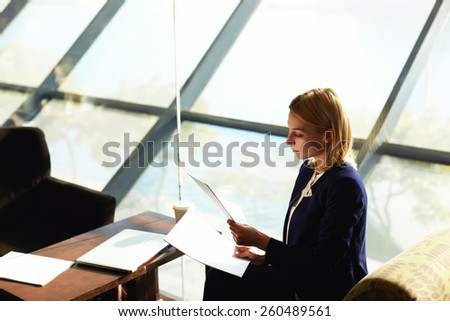 Side view charming blonde hair business woman examining paperwork sitting in modern restaurant next to the big window, businesswoman examining paperwork - stock photo