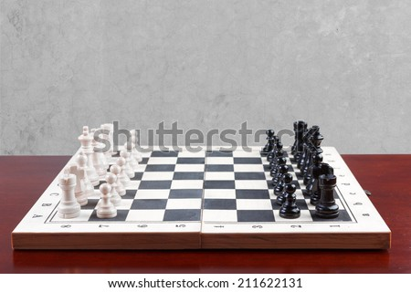 side view chess board set up to begin a game against concrete wall with clipping path - stock photo