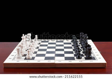 side view chess board set up to begin a game on black background with clipping path - stock photo