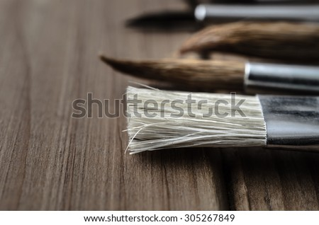 Side view close up of a variety of artist's paintbrushes, laid out in a row on a wood plank table. - stock photo