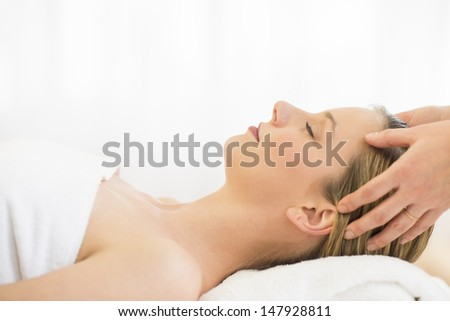 Side view close-up of beautiful young woman receiving head massage at health spa - stock photo