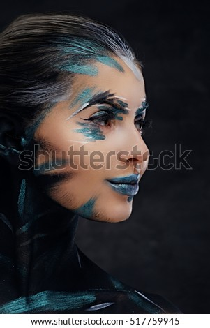 Side view close up portrait of a woman with artistic make up on dark background.