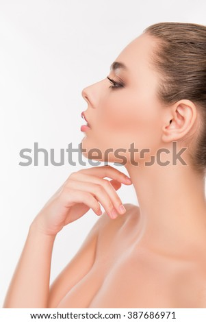 Side view, close up portrait of sensitive woman touching her neck - stock photo