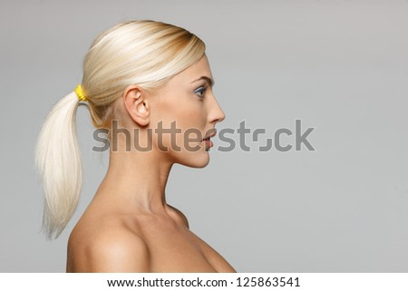 Side view closeup of beautiful blond woman looking forward over gray background - stock photo