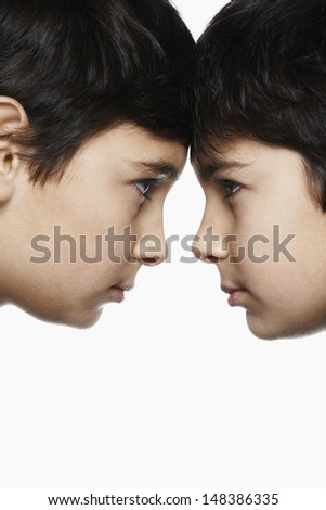 Side view closeup of preadolescent brothers with head to head isolated over white background - stock photo
