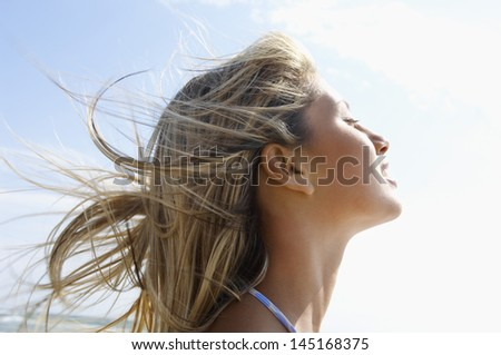 Side view closeup of young woman with eyes closed enjoying sunlight against sky at beach - stock photo