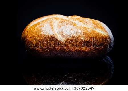 Side view closeup on bread roll, isolated on black background with reflection.