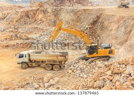 side view excavator loading crushed rock on dumper truck at dolomite mines site - stock photo