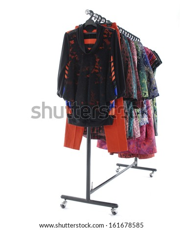 Side view female clothes with coat and trousers hanging on clothes rack on white - stock photo