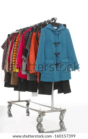 Side view female clothes with coat hanging on clothes rack on white - stock photo