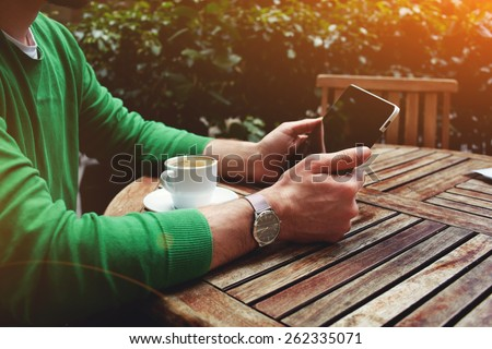 Side view freelancer sitting on the terrace with cup of coffee and touch screen tablet while having a break, man's hands holding digital tablet sitting at wooden table on the terrace of cafe, flare - stock photo