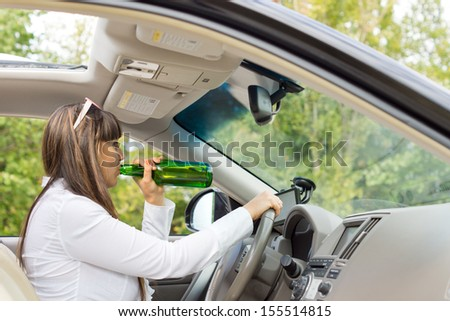 Side view from inside the vehicle of an alcoholic woman driver drinking and driving her car posing a threat to the safety of other motorists - stock photo