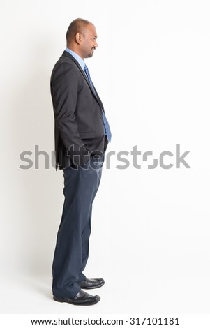 Side view full body mature Indian business man looking forward, standing on plain background. - stock photo