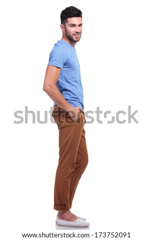 side view full body picture of a young casual man with hands in his pockets looking at the camera - stock photo