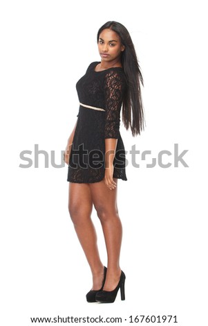 Side view full body portrait of an attractive young woman in black dress - stock photo