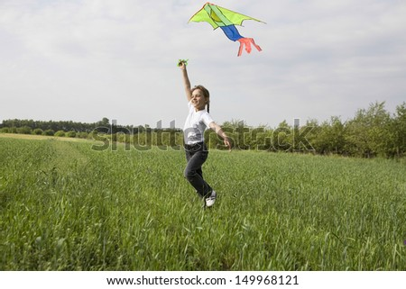 Side view full length of a young girl flying kite in the field