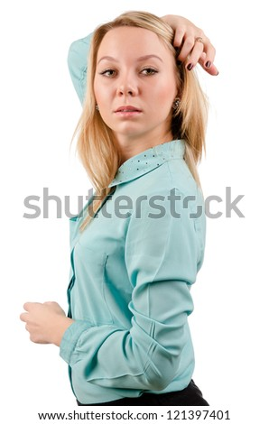 Side view half body portrait of a haughty young woman with a serious expression pulling her blonde hair back off her face with her hand - stock photo