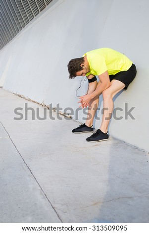 Side view image of exhausted male runner leaned the knees taking break after intensive and hard training in urban setting, young sports build man listen to music and rest after active workout outdoors - stock photo