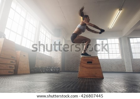 Side view image of fit young woman doing a box jump exercise. Muscular woman doing a box squat at the gym - stock photo