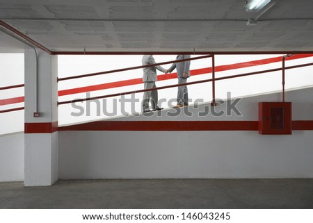 Side view lowsection of two businessmen shaking hands on ramp in parking garage - stock photo