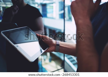 Side view male person using digital tablet, business man or freelancer working on touch pad in elevator, businessman executive using wireless devices in modern office, young successful browsing on pad - stock photo