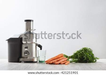 Side view metallic professional juicer with empty glass is prepared to make tasty juice for breakfast from fresh carrots lying on wooden table. Isolated on white background in cafe shop - stock photo