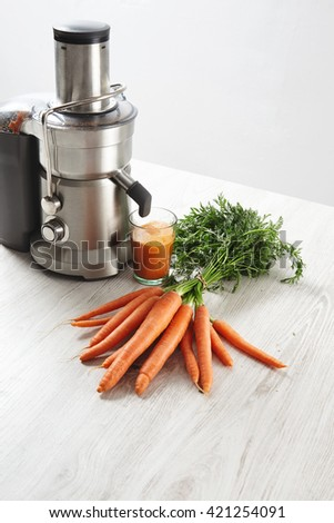 Side view metallic professional juicer with glass filled with tasty juice for breakfast from organic farm carrots lying on wooden table. Isolated on white background in cafe shop - stock photo