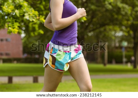 Side view mid section of healthy and beautiful young woman jogging in park - stock photo