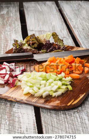 side view of a bamboo cutting board with chef's knife with freshly chopped organic carrots, lettuce, celery, and radishes on an old barn wood table - stock photo