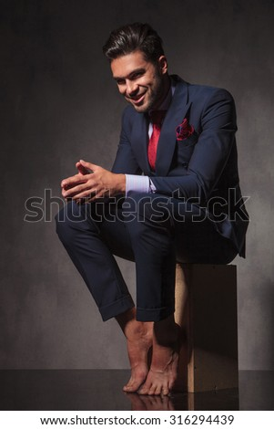 Side view of a barefoot business man smiling while holding his hands together.