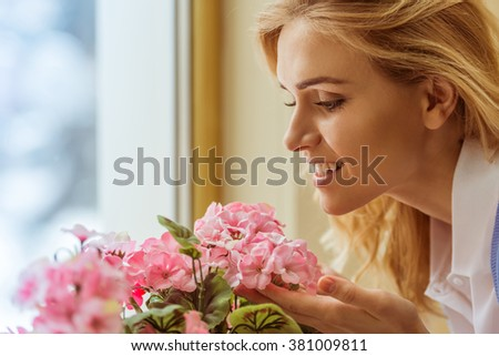 Side view of a beautiful young woman enjoying the scent of flowers, close-up