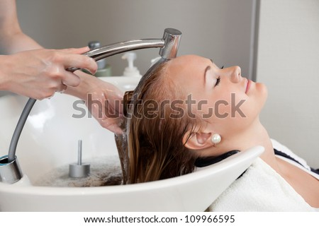 Side view of a beautiful young woman getting a hair washed by hairdresser at salon - stock photo