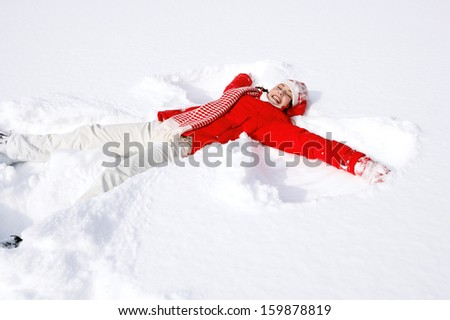 Side view of a beautiful young woman laying down on a frozen snow lake moving her arms and legs up and down creating an angel figure shape, playing games during a sunny winter  vacation. - stock photo
