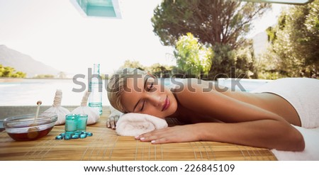 Side view of a beautiful young woman lying on massage table at spa center - stock photo