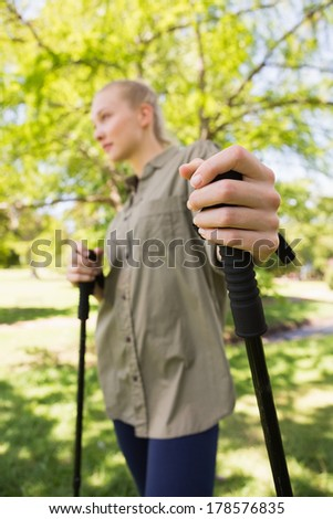 Side view of a beautiful young woman Nordic walking in the park - stock photo