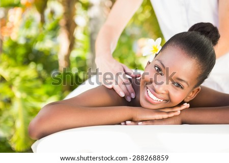 Side view of a beautiful young woman receiving massage at health farm - stock photo