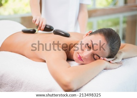 Side view of a beautiful young woman receiving stone massage at health farm - stock photo