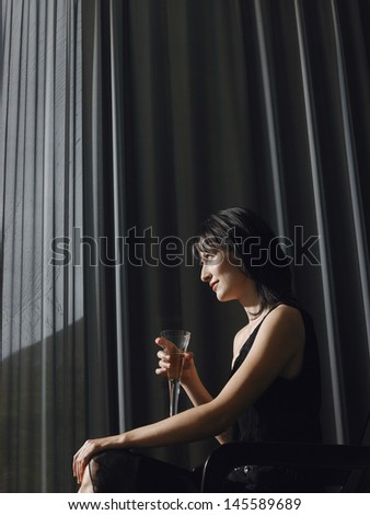 Side view of a beautiful young woman with champagne sitting on chair in front of curtains - stock photo