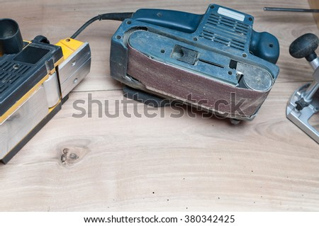 Side view of a belt sander and electric planer on table sanding surface - stock photo
