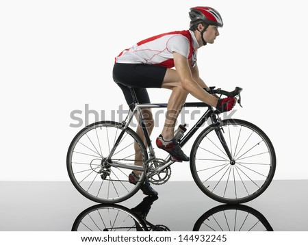 Side view of a bicyclist mounted on bicycle against white background - stock photo