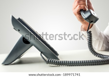 Side view of a black business landline telephone with the receiver held by a male hand with white shirt sleeve. - stock photo