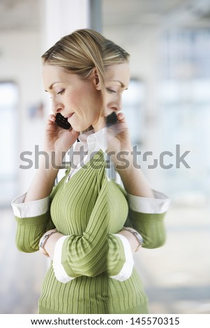 Side view of a blond businesswoman using mobile phone in office