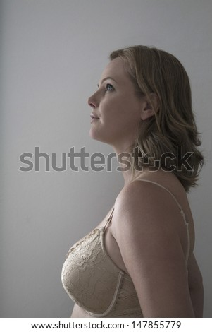 Side view of a blond woman in bra against gray background - stock photo