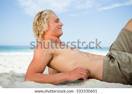 Side view of a blonde man lying on the beach while sunbathing - stock photo