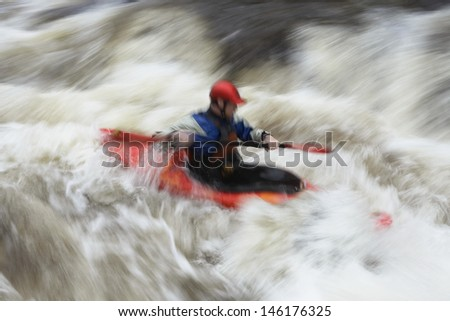 Side view of a blurred man kayaking in rough river - stock photo