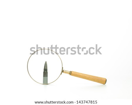 side view of a bullet seen through a magnifying glass, with a white background - stock photo