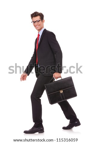 side view of a business man holding a briefcase and walking forward while looking at the camera - stock photo